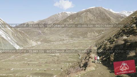 Купить «Two backpackers on the trekking Larke Pass in Nepal. Manaslu area.», видеоролик № 28688326, снято 18 июня 2018 г. (c) Dzmitry Astapkovich / Фотобанк Лори