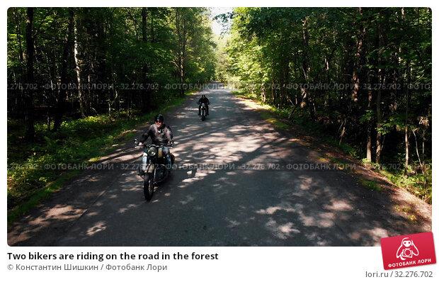 Купить «Two bikers are riding on the road in the forest», фото № 32276702, снято 20 октября 2019 г. (c) Константин Шишкин / Фотобанк Лори
