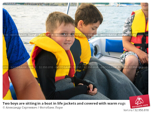 Two boys are sitting in a boat in life jackets and covered with warm rugs. Стоковое фото, фотограф Александр Сергеевич / Фотобанк Лори