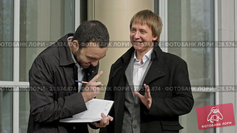 Купить «Two businessmen meeting outside of office building, smiling.», видеоролик № 28574874, снято 10 октября 2015 г. (c) Vasily Alexandrovich Gronskiy / Фотобанк Лори