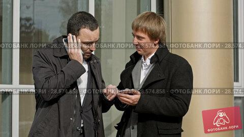 Купить «Two businessmen talking on mobile phone and reading message», видеоролик № 28574858, снято 10 октября 2015 г. (c) Vasily Alexandrovich Gronskiy / Фотобанк Лори