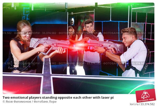 Купить «Two emotional players standing opposite each other with laser pi», фото № 33374582, снято 27 августа 2018 г. (c) Яков Филимонов / Фотобанк Лори