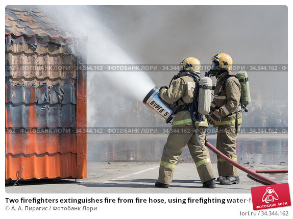 Two firefighters extinguishes fire from fire hose, using firefighting water-foam barrel with air-mechanical foam (2019 год). Редакционное фото, фотограф А. А. Пирагис / Фотобанк Лори