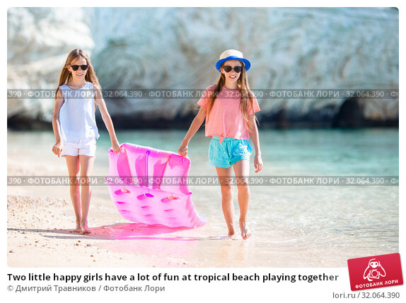 Two little happy girls have a lot of fun at tropical beach playing together. Стоковое фото, фотограф Дмитрий Травников / Фотобанк Лори