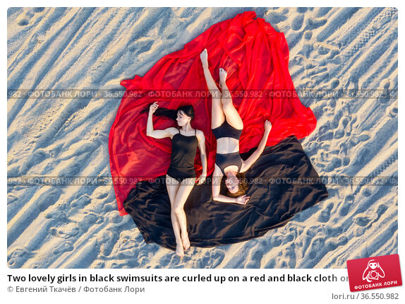 Two lovely girls in black swimsuits are curled up on a red and black cloth on a sandy beach. View from above. Стоковое фото, фотограф Евгений Ткачёв / Фотобанк Лори