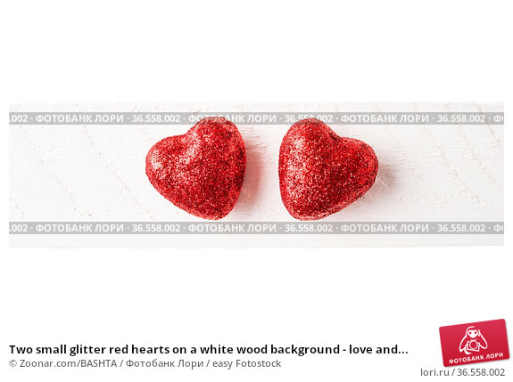 Two small glitter red hearts on a white wood background - love and... Стоковое фото, фотограф Zoonar.com/BASHTA / easy Fotostock / Фотобанк Лори