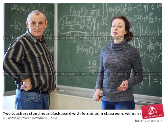Купить «Two teachers stand near blackboard with formulas in classroom, woman speaks», фото № 25838618, снято 7 апреля 2016 г. (c) Losevsky Pavel / Фотобанк Лори