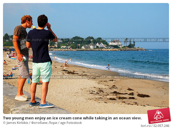 Two young men enjoy an ice cream cone while taking in an ocean view. Стоковое фото, фотограф James Kirkikis / age Fotostock / Фотобанк Лори