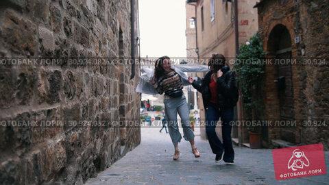 Купить «Two young women rush out of the building in a hurry and put on jackets», видеоролик № 30924082, снято 16 июня 2019 г. (c) Константин Шишкин / Фотобанк Лори