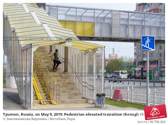 Купить «Tyumen, Russia, on May 9, 2019: Pedestrian elevated transition through the highway to summertime», фото № 30756262, снято 9 мая 2019 г. (c) Землянникова Вероника / Фотобанк Лори