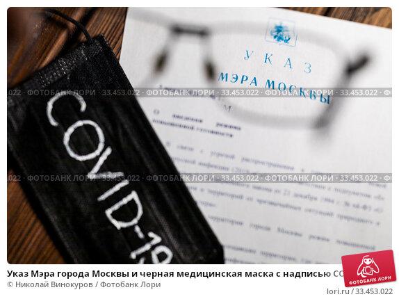 Указ Мэра города Москвы и черная медицинская маска с надписью COVID-19 лежат на столе. Стоковое фото, фотограф Николай Винокуров / Фотобанк Лори