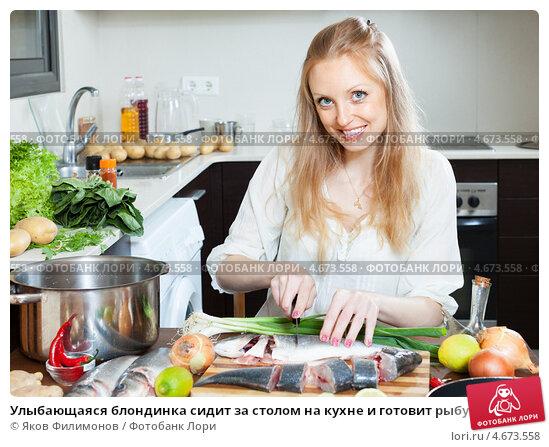 Купить «Улыбающаяся блондинка сидит за столом на кухне и готовит рыбу», фото № 4673558, снято 15 мая 2013 г. (c) Яков Филимонов / Фотобанк Лори