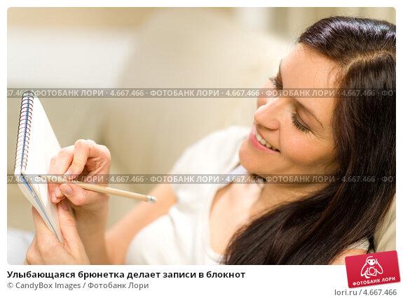 Улыбающаяся брюнетка делает записи в блокнот. Стоковое фото, фотограф CandyBox Images / Фотобанк Лори