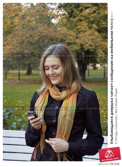 Улыбающаяся девушка читает сообщение на мобильном телефоне, фото № 98046, снято 26 апреля 2017 г. (c) Игорь Соколов / Фотобанк Лори