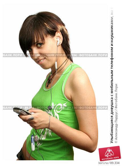 Улыбающаяся девушка с мобильным телефоном и наушниками, на белом фоне, фото № 89334, снято 23 мая 2007 г. (c) Александр Паррус / Фотобанк Лори
