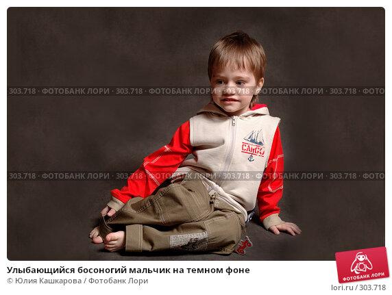 Улыбающийся босоногий мальчик на темном фоне, фото № 303718, снято 23 марта 2008 г. (c) Юлия Кашкарова / Фотобанк Лори