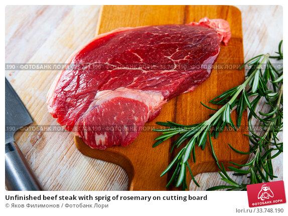 Купить «Unfinished beef steak with sprig of rosemary on cutting board», фото № 33748190, снято 4 июля 2020 г. (c) Яков Филимонов / Фотобанк Лори