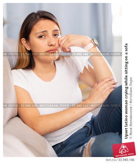 Upset latino woman crying while sitting on a sofa. Стоковое фото, фотограф Яков Филимонов / Фотобанк Лори
