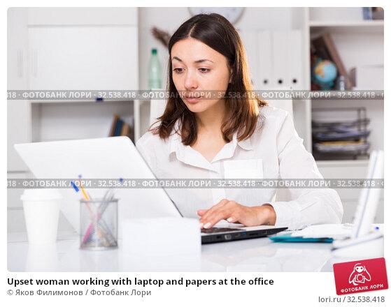 Купить «Upset woman working with laptop and papers at the office», фото № 32538418, снято 1 мая 2018 г. (c) Яков Филимонов / Фотобанк Лори