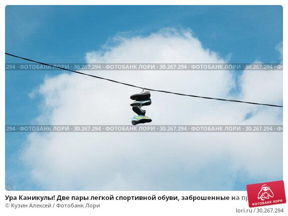 Купить «Ура Каникулы! Две пары легкой спортивной обуви заброшенные на провода на фоне неба с белым облаком», фото № 30267294, снято 27 октября 2018 г. (c) Кузин Алексей / Фотобанк Лори