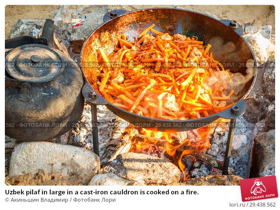 Купить «Uzbek pilaf in large in a cast-iron cauldron is cooked on a fire.», фото № 29438562, снято 15 июля 2017 г. (c) Акиньшин Владимир / Фотобанк Лори