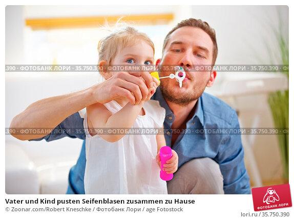 Vater und Kind pusten Seifenblasen zusammen zu Hause. Стоковое фото, фотограф Zoonar.com/Robert Kneschke / age Fotostock / Фотобанк Лори
