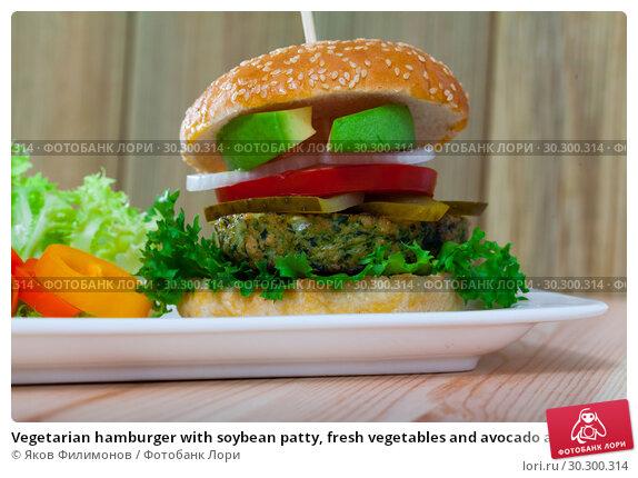 Купить «Vegetarian hamburger with soybean patty, fresh vegetables and avocado at plate», фото № 30300314, снято 20 апреля 2019 г. (c) Яков Филимонов / Фотобанк Лори