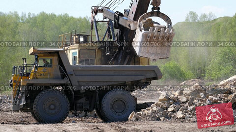 Video of excavator loads stones onto a dump truck on a open pit. Редакционное видео, видеограф Serg Zastavkin / Фотобанк Лори