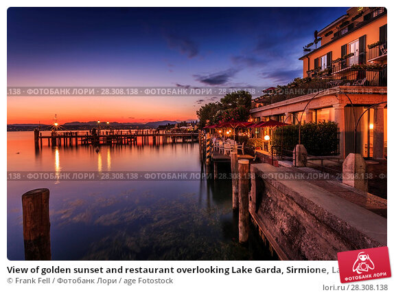 Купить «View of golden sunset and restaurant overlooking Lake Garda, Sirmione, Lake Garda, Lombardy, Italian Lakes, Italy, Europe», фото № 28308138, снято 21 августа 2017 г. (c) age Fotostock / Фотобанк Лори