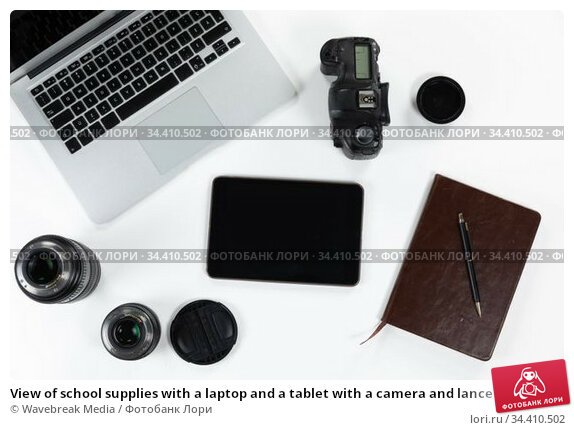 View of school supplies with a laptop and a tablet with a camera and lance in a white background. Стоковое фото, агентство Wavebreak Media / Фотобанк Лори
