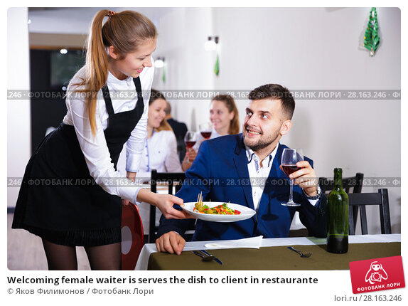 Купить «Welcoming female waiter is serves the dish to client in restaurante», фото № 28163246, снято 18 декабря 2017 г. (c) Яков Филимонов / Фотобанк Лори