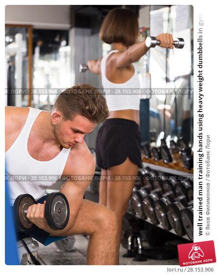 well trained man training hands using heavy weight dumbbells in gym indoors. Стоковое фото, фотограф Яков Филимонов / Фотобанк Лори