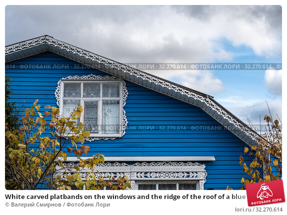 Купить «White carved platbands on the windows and the ridge of the roof of a blue house», фото № 32270614, снято 5 октября 2019 г. (c) Валерий Смирнов / Фотобанк Лори