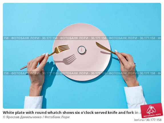Купить «White plate with round whatch shows six o'clock served knife and fork in a girl's hands on a blue background. Time to eat and diet concept. Top view.», фото № 30177158, снято 5 февраля 2019 г. (c) Ярослав Данильченко / Фотобанк Лори