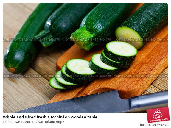 Whole and sliced fresh zucchini on wooden table. Стоковое фото, фотограф Яков Филимонов / Фотобанк Лори