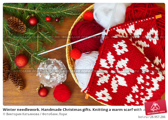 Купить «Winter needlework. Handmade Christmas gifts. Knitting a warm scarf with a New Year red and white pattern and a spruce branches with festive decorations on wooden table», фото № 28957286, снято 19 июля 2018 г. (c) Виктория Катьянова / Фотобанк Лори