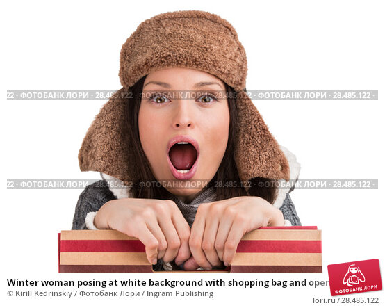 Купить «Winter woman posing at white background with shopping bag and opened mouth», фото № 28485122, снято 17 декабря 2012 г. (c) Ingram Publishing / Фотобанк Лори