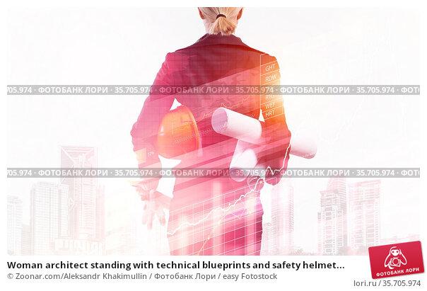 Woman architect standing with technical blueprints and safety helmet... Стоковое фото, фотограф Zoonar.com/Aleksandr Khakimullin / easy Fotostock / Фотобанк Лори