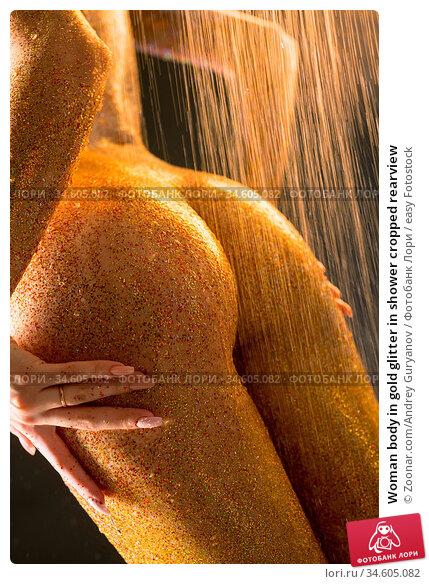 Woman body in gold glitter in shower cropped rearview. Стоковое фото, фотограф Zoonar.com/Andrey Guryanov / easy Fotostock / Фотобанк Лори