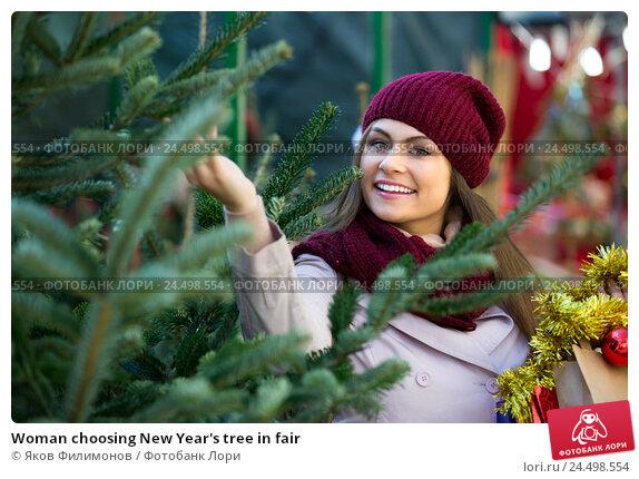 Купить «Woman choosing New Year's tree in fair», фото № 24498554, снято 21 ноября 2019 г. (c) Яков Филимонов / Фотобанк Лори