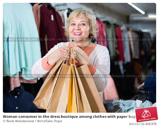 Купить «Woman consumer in the dress boutique among clothes with paper bags», фото № 32428878, снято 20 декабря 2017 г. (c) Яков Филимонов / Фотобанк Лори