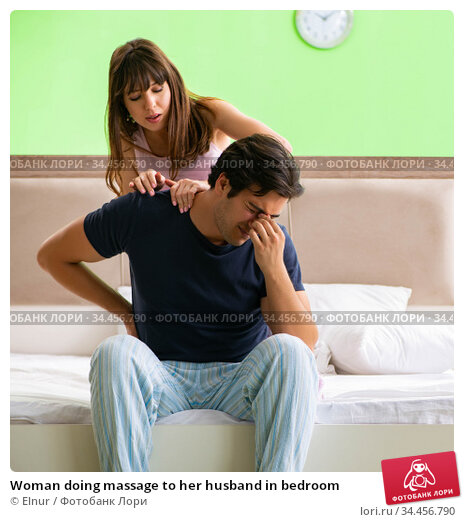 Woman doing massage to her husband in bedroom. Стоковое фото, фотограф Elnur / Фотобанк Лори