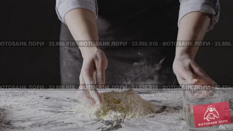 Купить «Woman hands pour water into flour and eggs to knead homemade gough for preparation pasta on a black background. Slow motion, Full HD video, 240fps, 1080p.», видеоролик № 33886918, снято 4 июля 2020 г. (c) Ярослав Данильченко / Фотобанк Лори