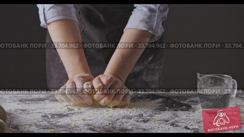 Купить «Woman hands put flour on a table and knead homemade gough for preparation pasta on a black background. Slow motion, Full HD video, 240fps, 1080p.», видеоролик № 33704962, снято 31 августа 2018 г. (c) Ярослав Данильченко / Фотобанк Лори