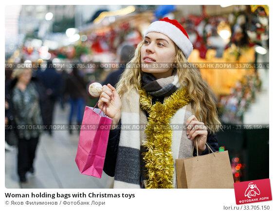 Купить «Woman holding bags with Christmas toys», фото № 33705150, снято 20 декабря 2018 г. (c) Яков Филимонов / Фотобанк Лори