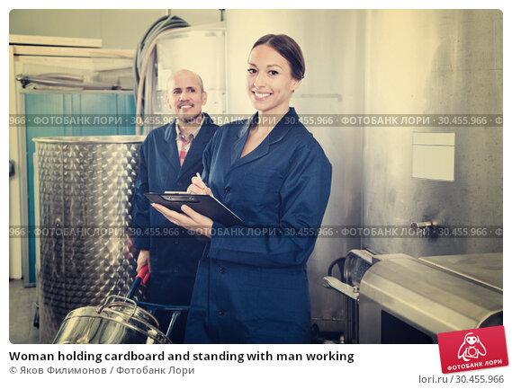 Woman holding cardboard and standing with man working. Стоковое фото, фотограф Яков Филимонов / Фотобанк Лори