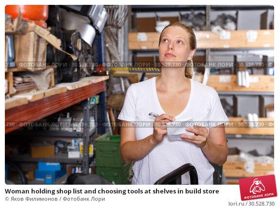 Купить «Woman holding shop list and choosing tools at shelves in build store», фото № 30528730, снято 20 сентября 2018 г. (c) Яков Филимонов / Фотобанк Лори