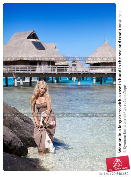 Купить «Woman in a long dress with a rose in hand in the sea and traditional huts on  background», фото № 29540682, снято 18 июня 2011 г. (c) Куликов Константин / Фотобанк Лори