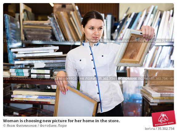 Woman is choosing new picture for her home in the store. Стоковое фото, фотограф Яков Филимонов / Фотобанк Лори