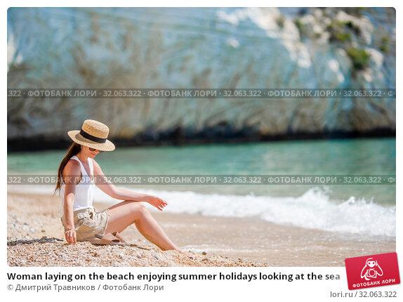 Woman laying on the beach enjoying summer holidays looking at the sea. Стоковое фото, фотограф Дмитрий Травников / Фотобанк Лори